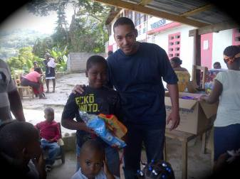 Nicolas Duvalier posing with kids at a toy distribution event for Christmas.